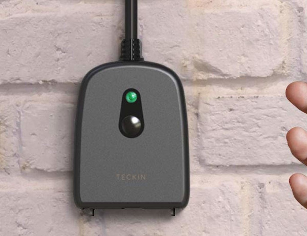 Smart outdoor plug on a white brick wall