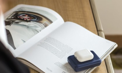Wireless power bank charging Apple AirPods on an open book