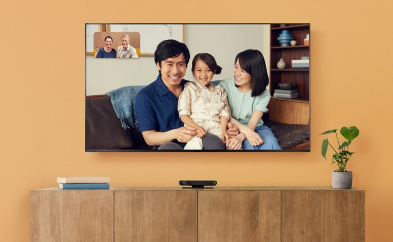 A TV with a black Facebook portal below it and a mother, father, and child on the TV screen.