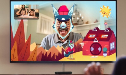A TV is hanging on the wall, and there is an image on the TV of a man with a funny wolf filter over his face.