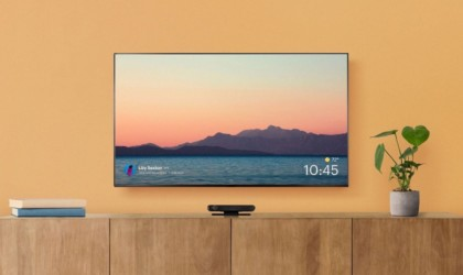 A TV is hanging on an orange wall, showing an image of water and mountains, and thre is a black device under the TV.