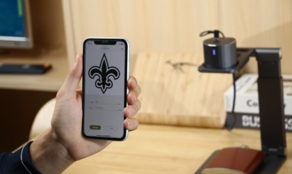 A person is holding up a smart phone with a fleur de lis image on it, in front of an engraving machine.
