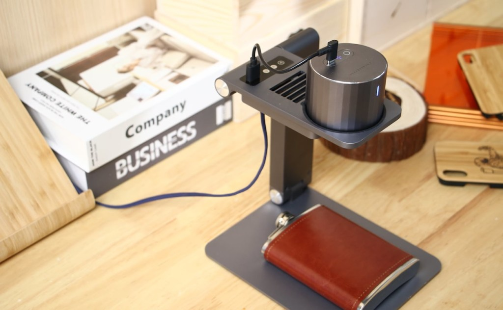 A top-down view of an engraving machine with a pocket flask under it.