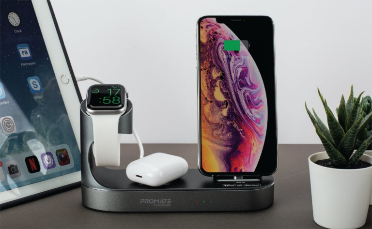 A charging bank is on a desk and it has an iPhone, AirPods, and an Apple Watch charging on it.