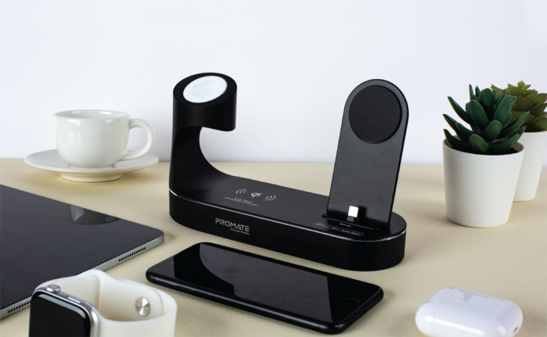 A black charging dock sitting on a desk next to an iPhone and an Apple Watch