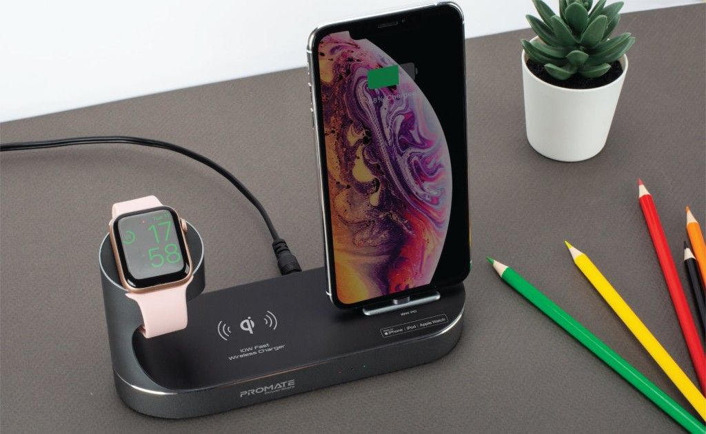 A black charging port is on a desk with an Apple Watch and an iPhone on it.