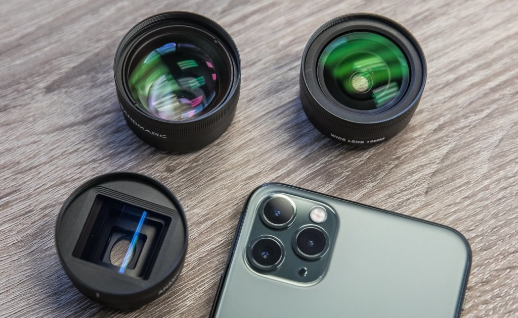 An iPhone is face down, and it has three small photography lenses around it.