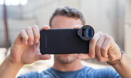 A man is holding up a black iPhone to take a picture, and the iPhone has a small photography lens attached to it.