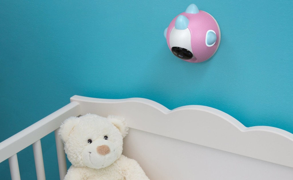 A small pink and white camera is mounted on a blue wall above a crib with a stuffed teddy bear in it.