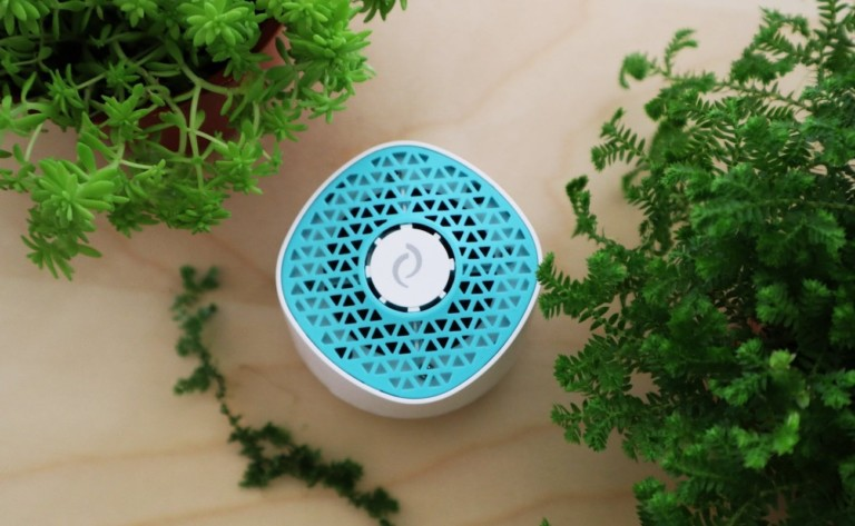 A blue and white odor eliminating device is on a wooden background, surrounded by green leaves.