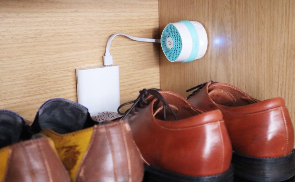 A small white and blue odor gadget is mounted to a shelf above a row of men's dress shoes.