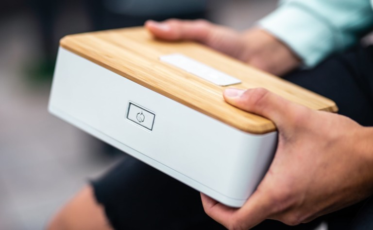 A person is holding a white lunch box with a wood lid.