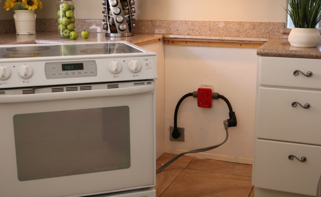 A stove is pulled out to show the red sensor on the wall behind it.