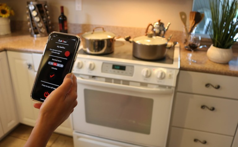 A woman is using a smartphone in front of a stove.