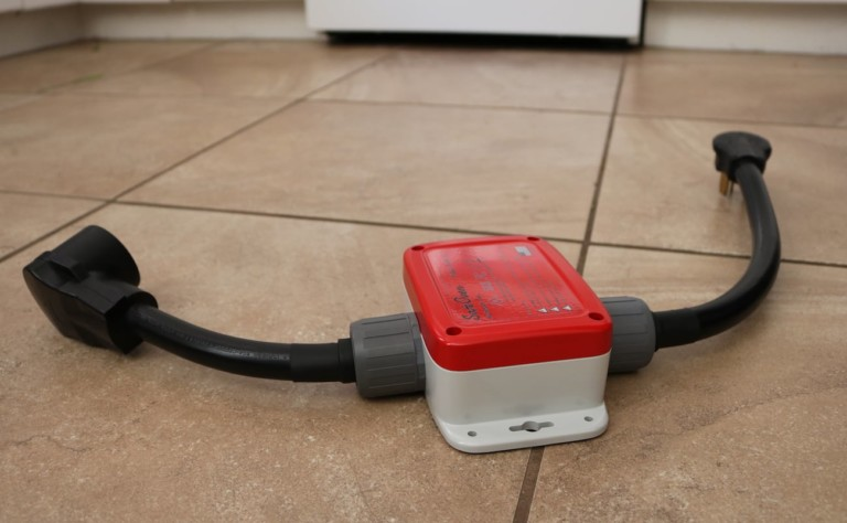 A red and white sensor with cords coming out of both sides in on a tile floor.