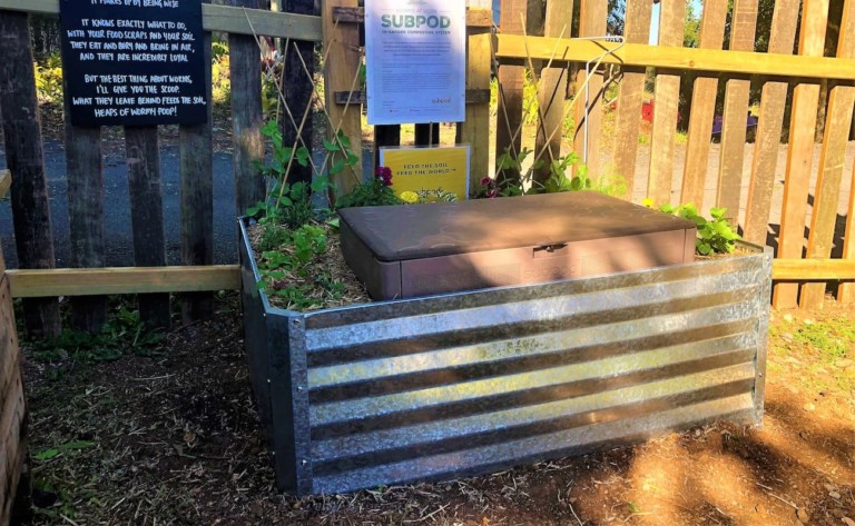 A brown composting box is inside of a metal container, against a fence with signs on it.