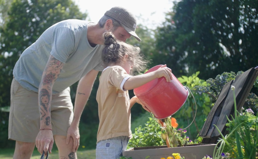 A man and a little girl empty food scraps into a brown composting box.