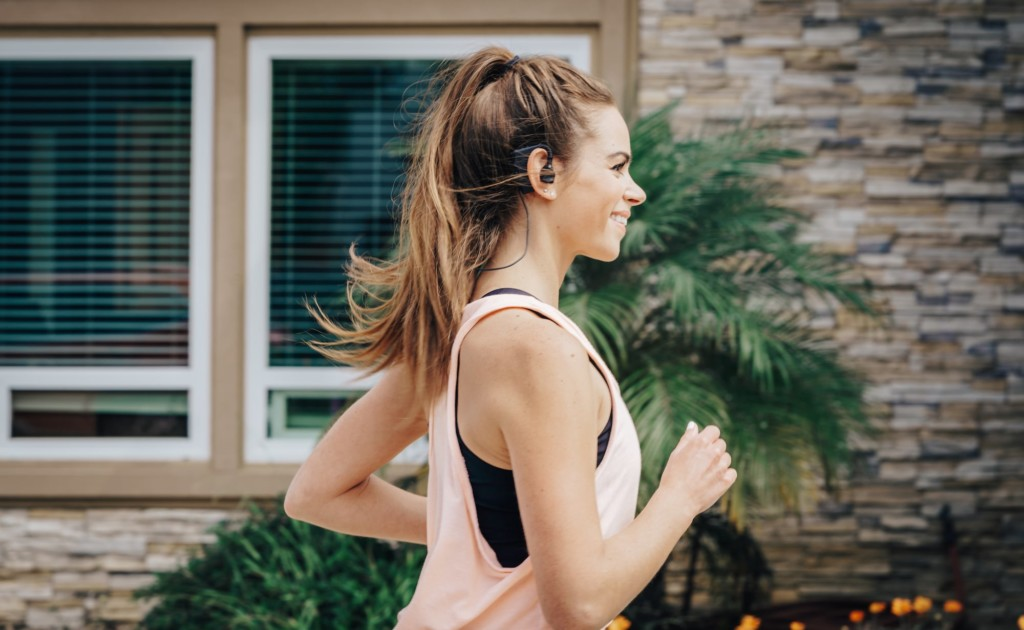 A woman is running outdoors, wearing earbuds.