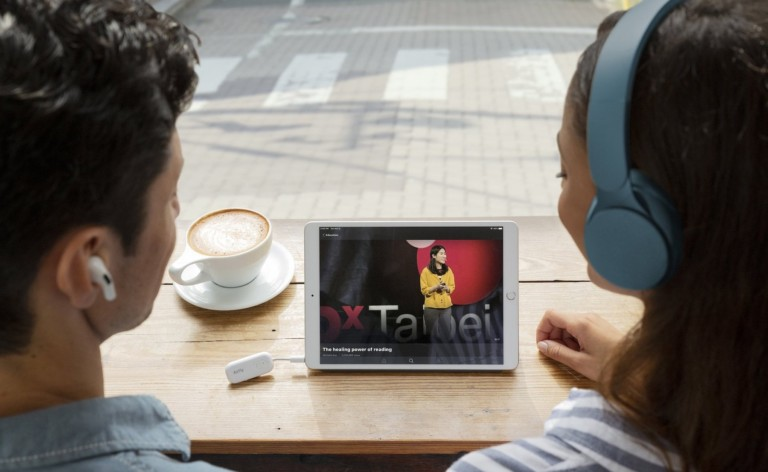 A man and a woman are watching a table, wearing headphone.