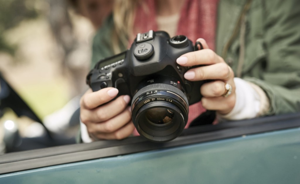 A woman is holding a camera that has a round black Tile on it.