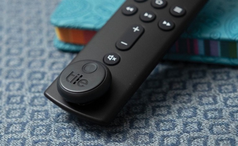 A black remote with a round black Tile on it.