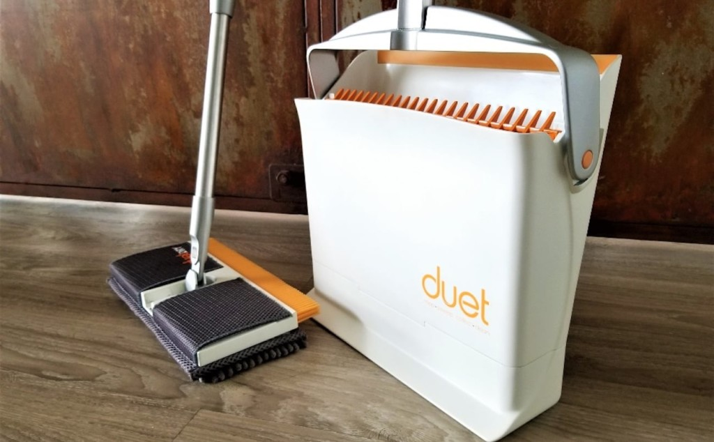 A broom is next to a white and orange bin.