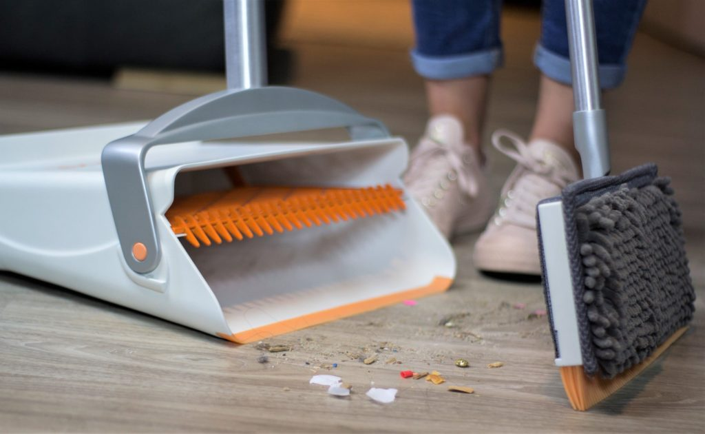 A woman is holding a dustpan and sweeping debris into it.