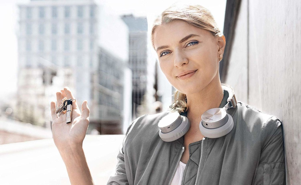 A woman with headphones around her next is holding a charger keyring.