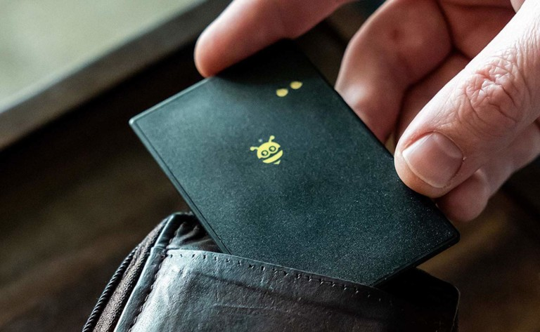 A person is sliding a black wallet finder with a bee on it into a wallet.