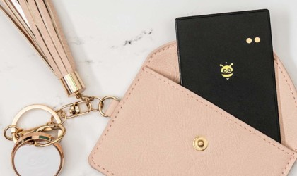 A light pink wallet with a black wallet finder card with a bee on it sticking out.