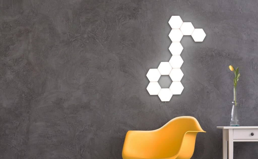 A modular lighting display in the shape of a music note is on a gray wall, with a yellow chair in front of it.