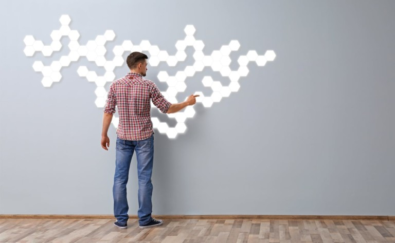 A man is standing in front of a wall with modular lights, touching a light.