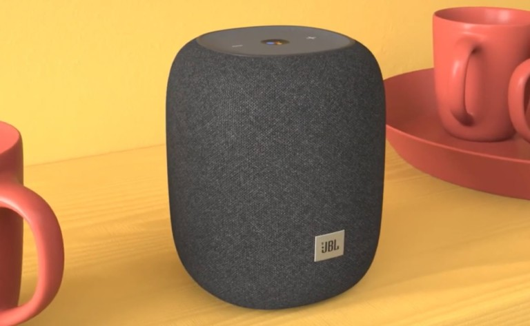 A small, round gray speaker against a yellow background.