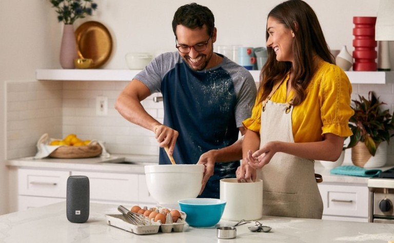 A man and a woman are in a kitchen making food, and there is a small, gray round speaker on the counter.