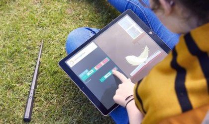A person is sitting outside and playing with a Harry Potter coding app on a tablet.