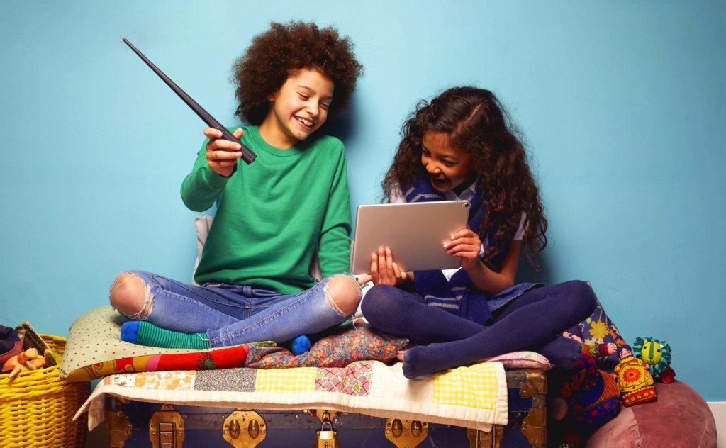 Two girls are smiling and sitting on a bed, playing with a Harry Potter coding wand and a tablet.