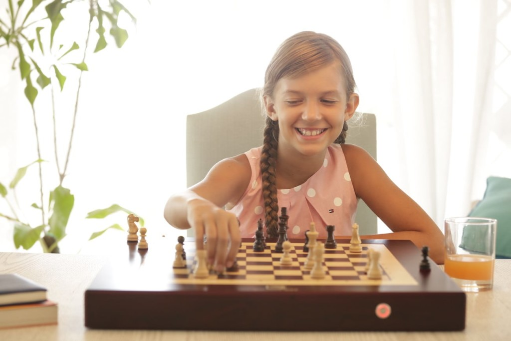 A little girl is smiling and playing with a chess set.