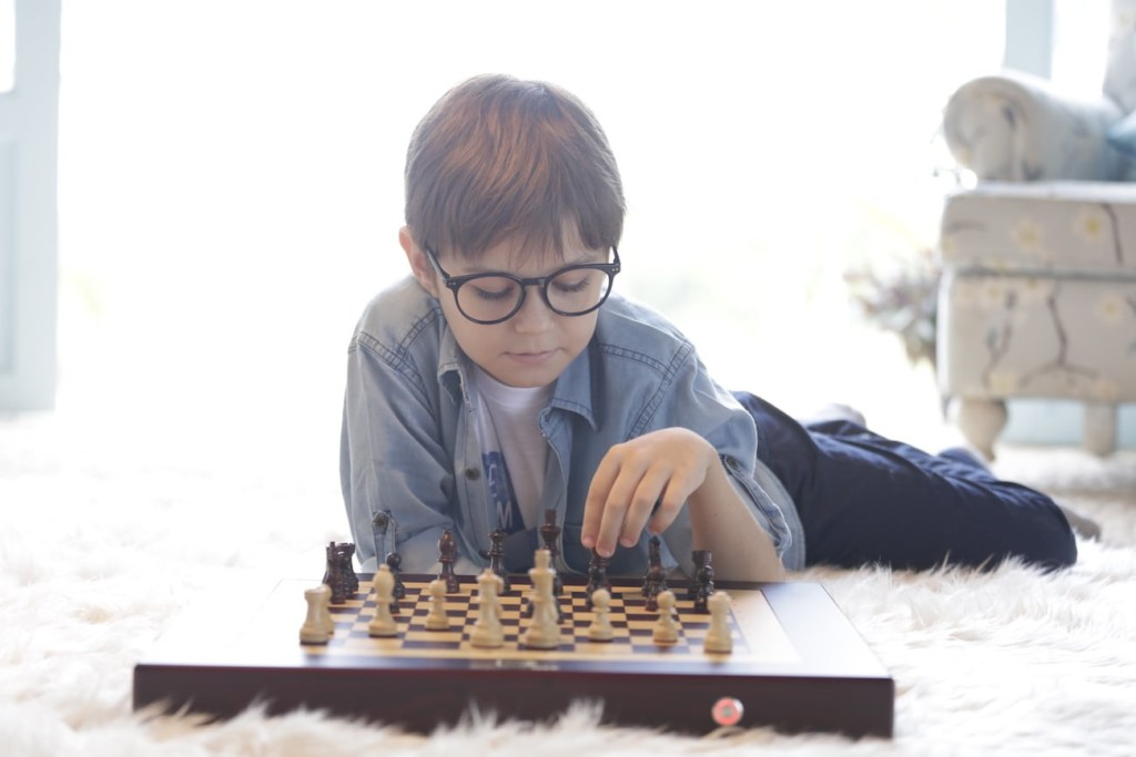 A little boy with glasses is playing with a chess set