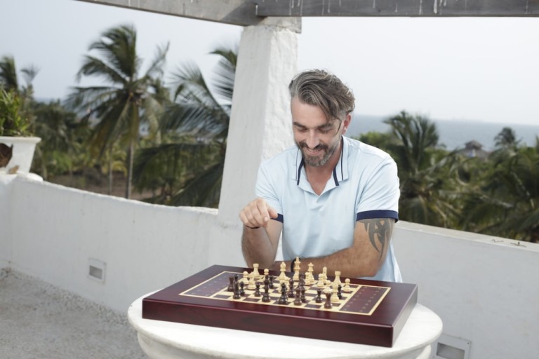 A man is smiling and playing with a chess set