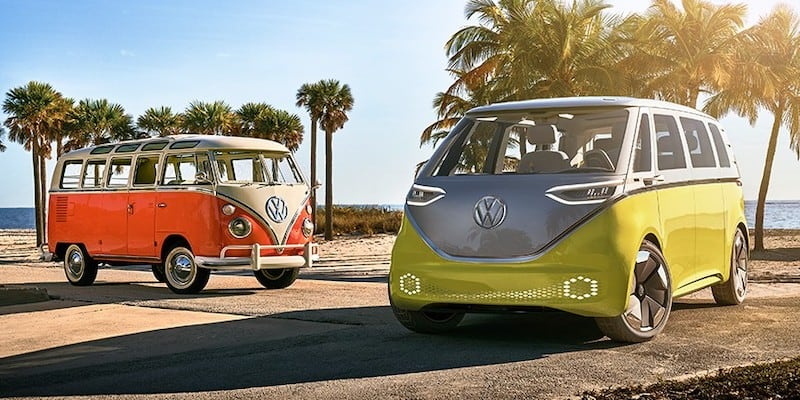 an old red VW Microbus next to the green and gray future vehicle electric version of it.