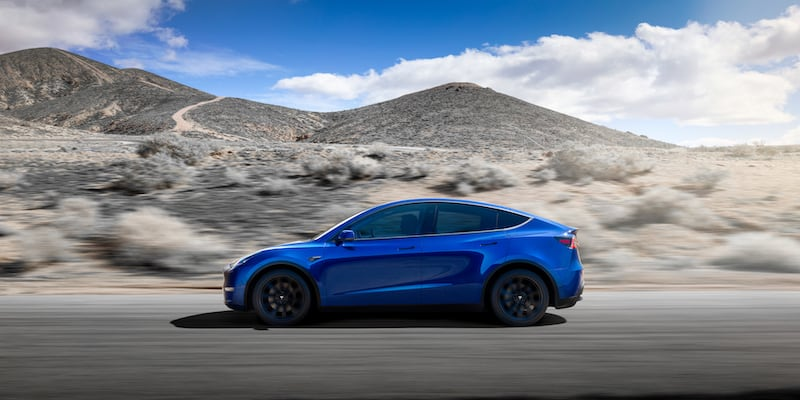 A blue Tesla future vehicle outdoors, with mountains in the background.