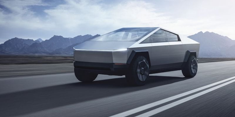 An image of a silver futuristic-looking Tesla pickup truck driving on a highway.