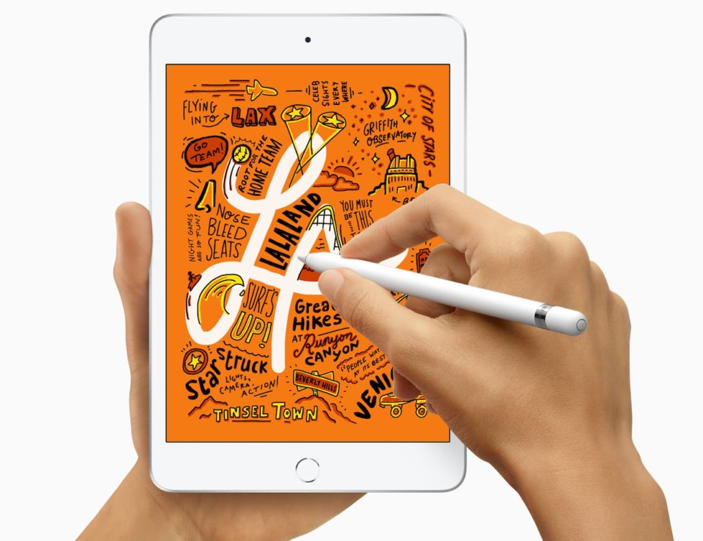 A pair of hands is holding an iPad Mini, and one hand is using an Apple Pencil to write on the screen.
