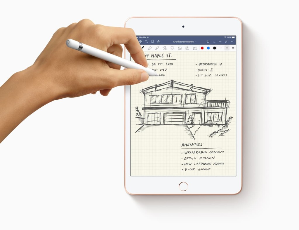 An iPad Mini on a white surface, with a hand holding an Apple Pencil above it