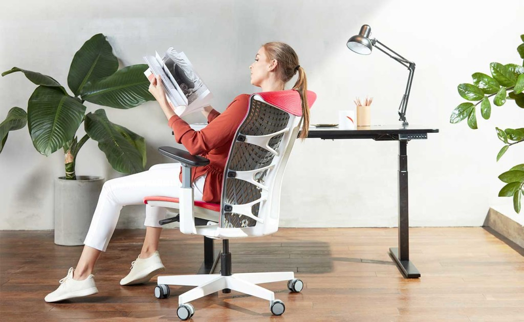 A woman is sitting in a white office chair and reading a book.