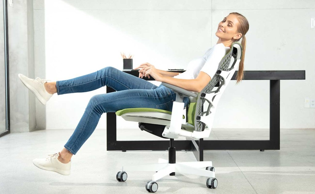 A woman is sitting in an office chair, slightly tilted back and smiling.