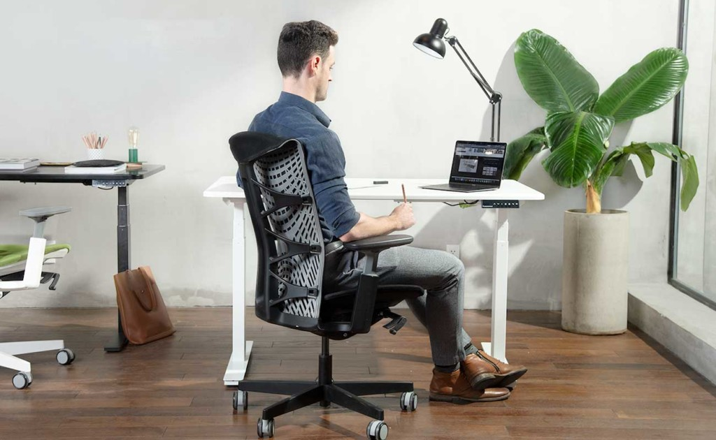 A man is sitting in a black office chair and working at a laptop.