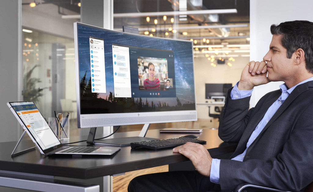 A man is sitting in a large office space in front of a curved computer monitor.