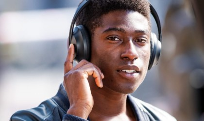 A man is looking at the camera, wearing a pair of black headphones, and lifted his hand to touch one ear cup.