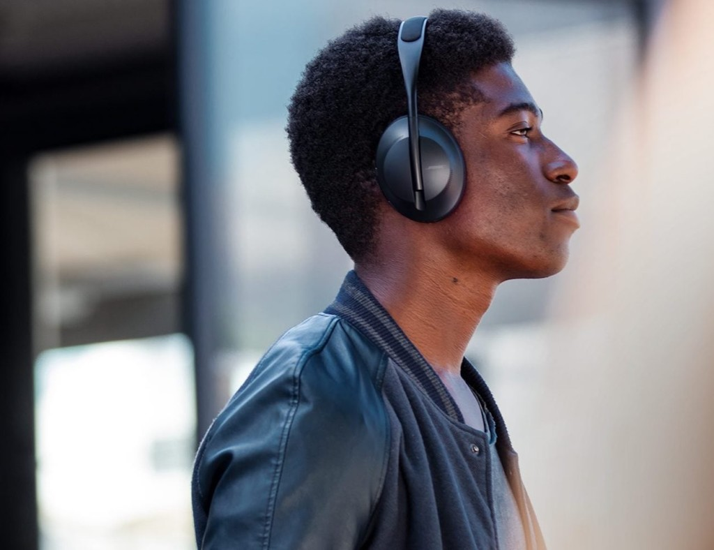 A side view of a man who is wearing a pair of black headphones.